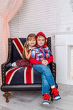 Girl and boy sitting on chair with a British flag Royalty Free Stock Photos