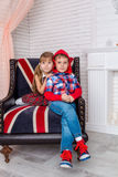Girl and boy sitting on chair with a British flag Stock Images