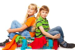 Girl and boy sitting in clothing basket Royalty Free Stock Photography