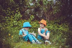 Girl and Boy Sitting on Grass Field Surrounded by Trees stock image
