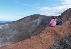 Girl and boy sitting on the rim of volcano crater Stock Photos