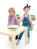 Girl and boy sitting at the table draw. Royalty Free Stock Images
