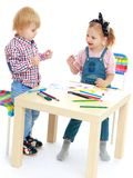 Girl and boy sitting at the table draw. Stock Photography