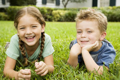 girl and boy smiling  lying on the grass Royalty Free Stock Images