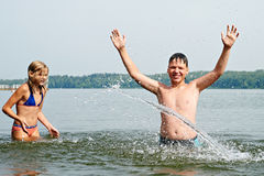 Girl and boy splash each other with water at beach. Girl and boy splash each other with water at the beach Stock Photo