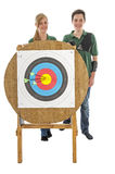 Girl and boy standing behind archery target Stock Photography