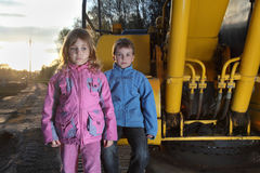 Girl and boy standing near crawler tractor Stock Images