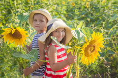 Girl and boy standing among sunflowers Royalty Free Stock Images