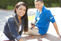 Girl and boy students relaxing outdoors. A teenage girl and boy sitting outdoors relaxing on a brick platform Stock Photo