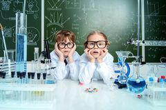 Girl and boy. Surprised girl and boy scientists are conducting an experiment in the laboratory. Educational concept. Early development of children royalty free stock photos