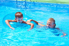Girl and boy swimming into resort pool Royalty Free Stock Photo