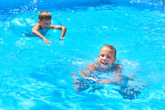 Girl and boy swimming into resort pool Royalty Free Stock Images