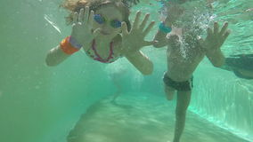 Girl and boy swimming under water stock footage