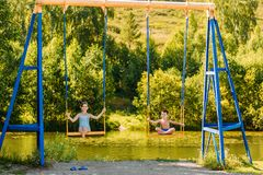 Girl and boy swing on big iron swing in summer. Brother and sister royalty free stock photos