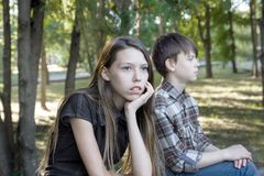 Girl and a boy teenagers are angry at each other. Bad relationship, resentment. Unhappy young girl tine sits with her back to the young man, resentment. The stock photos