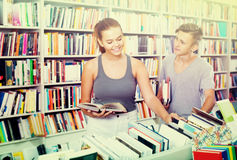 Girl and boy teenagers in book store Stock Images