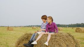 Girl and boy teenagers sitting on haystack at harvesting field. Happy boy and girl reading book on hay stack at autumn stock footage
