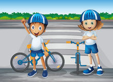 A girl and a boy with their bikes standing near the pedestrian l Royalty Free Stock Photography
