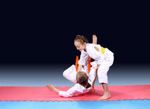 Girl and boy are trained judo throw on the mat Stock Image