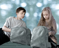 Girl and boy with travel backpacks sitting on the floor against the background of large window Royalty Free Stock Photos