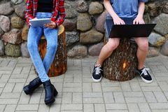 Girl and boy using laptop and tablet outdoors. Young teenage girl and boy sitting on cut tree trunks and using laptop and tablet on grey grunge decorative stone Royalty Free Stock Image