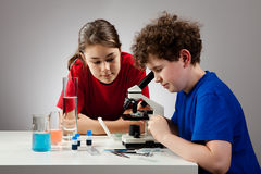 Girl and boy using microscope royalty free stock photography