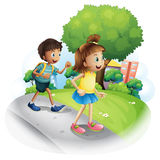 A girl and a boy walking along the street Stock Image