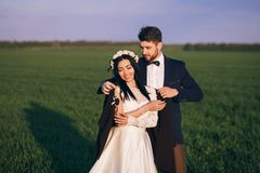 Girl and boy hugging in the field, cold evening, girl in a knitted sweater, gentle and loving young people, bride and groom royalty free stock photo