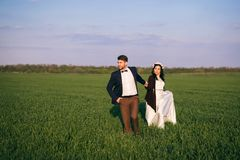 Girl and boy hugging in the field, cold evening, girl in a knitted sweater, gentle and loving young people, bride and groom royalty free stock photos