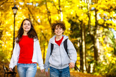 Girl and boy walking in park Stock Photo
