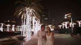 Girl and boy walking on the street the night Dubai. Among the glowing palms trees. UAE. stock video