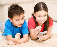 Girl and boy watching tv Stock Photos
