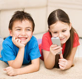 Girl and boy watching tv. Happy girl and boy watching tv, remote control Stock Images