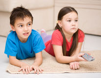 Girl and boy watching tv. Happy girl and boy watching tv, remote control Stock Photos