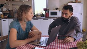Girl with boyfriend in apartment. Young couple or family home. Attractive caucasian woman and handsome man with beard sitting at the table in kitchen. People stock footage