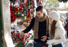 Girl with boyfriend choosing tradition catalan Christmas souven. Happy girl with boyfriend choosing tradition catalan Christmas souvenirs at Barcelona x-mas royalty free stock images