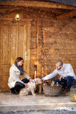Girl and boyfriend with dog in front of cottage Royalty Free Stock Photo