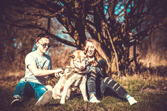Girl with boyfriend and her husky dog outdoor in the forest Royalty Free Stock Photos