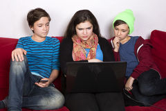 Girl and boys and a laptop Stock Photos