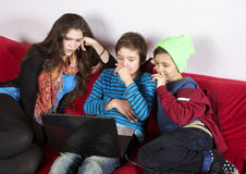 Girl and boys and a laptop Stock Photo