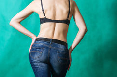 Girl in bra and blue jeans, posing with his back Royalty Free Stock Photography