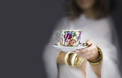 Girl  with bracelets  giving a colorful cup Royalty Free Stock Photo