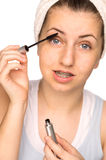 Girl with braces applying mascara isolated Royalty Free Stock Photography