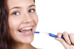 Girl with braces brushing her teeth. Happy girl with braces brushing her teeth Stock Photos