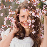 Girl with braces holding blossoming tree branch Royalty Free Stock Photo