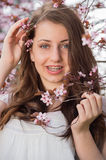 Girl with braces holding blossoming tree branch Stock Image