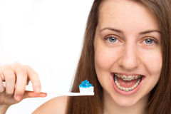 Girl with braces holding toothbrush isolated Royalty Free Stock Images