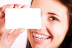 Girl with braces presenting business card Stock Image