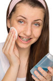 Girl with braces using makeup removal Stock Photos