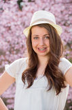 Girl with braces wearing hat spring blossom Stock Image